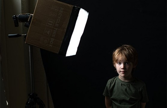 A boy stands looking at a photographer with a softbox made from a cardboard box to one side.