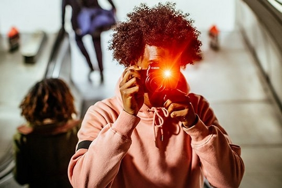 A man wearing a pink sweatshirt holds a Canon camera to his face. The flash casts an orange light.