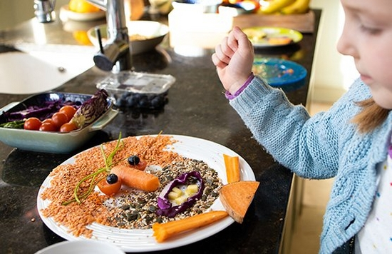 A young girl creating a face out of food on a plate.