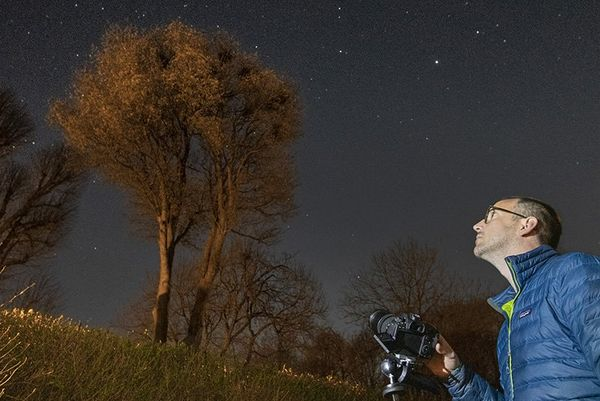 A photographer sets up a tripod in his garden to take a photo of the night sky.