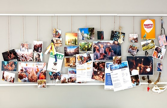 A selection of colourful home-printed cards and other items on a wall.
