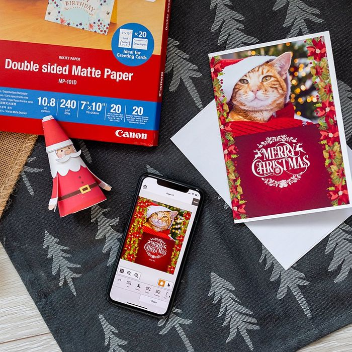 A home-printed Christmas card alongside crafted decorations and Canon Double-sided Matte Paper arranged on a cloth with a Christmas tree motif.