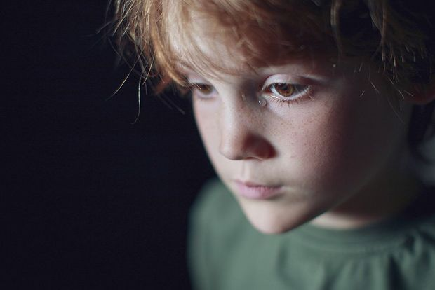 A portrait of a boy against a black background.