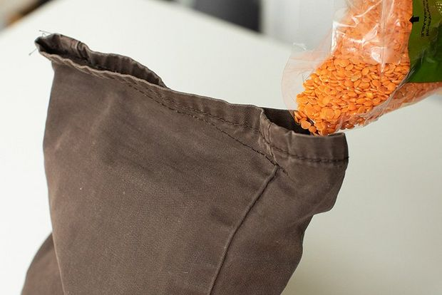 Red lentils being poured into the opening at the top of a cut-off trouser leg.