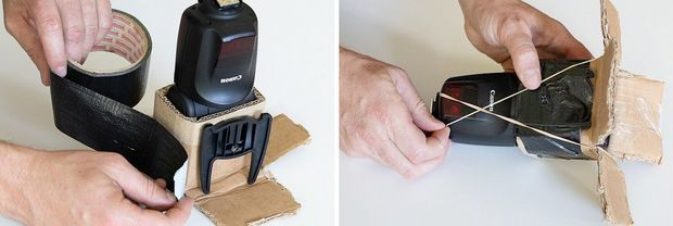Two hands use black tape to secure a cardboard sheath around a Speedlite flash.