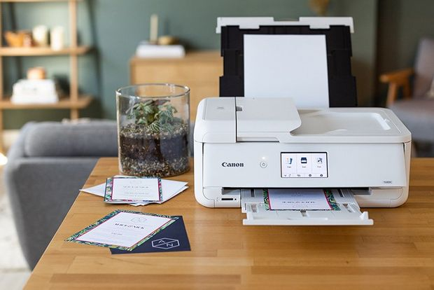 A Canon printer on a table in a living room.