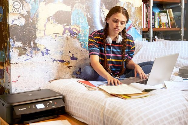 A teenage girl sits cross-legged on a bed, studying her textbooks. A Canon PIXMA TS5150 printer is on the table beside her.