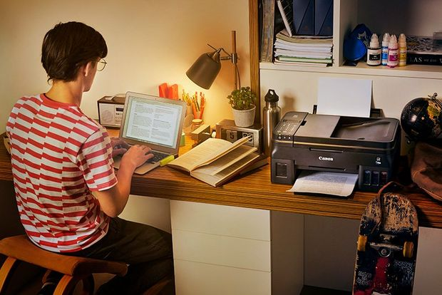 A teenage boy sits at his desk in his bedroom. A Canon G4500 printer is on the desk beside him.