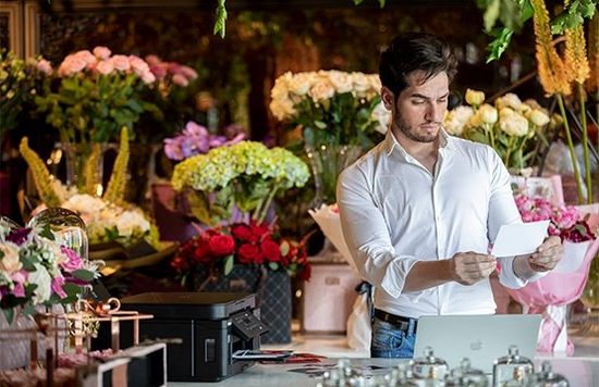In a room filled with flowers, a man holds a print he has made using a Canon PIXMA G6050 that can be seen on the table in front of him.