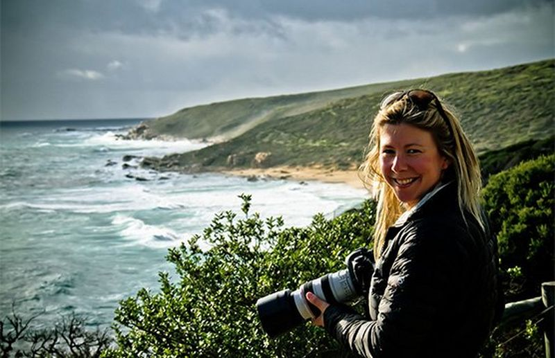 Photographer Camilla Rutherford smiles for the camera, waves lapping the shoreline behind her.