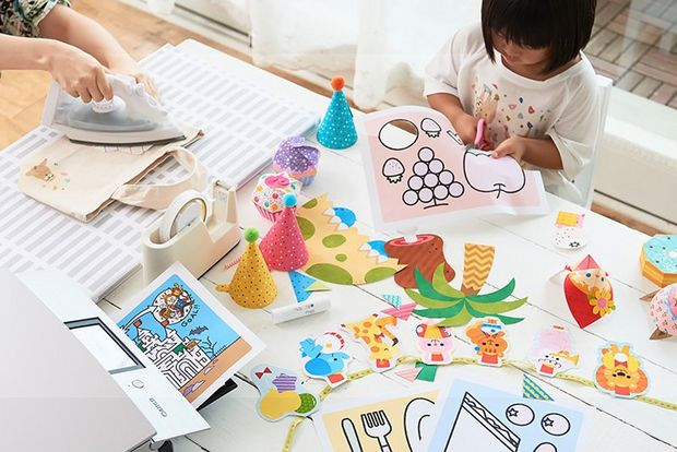 Woman and child's hands on desk filled with creative nick-nacks.