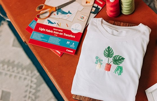 A white T-shirt with a printed embroidery pattern of houseplants, beside a pack of Canon iron-on transfers.