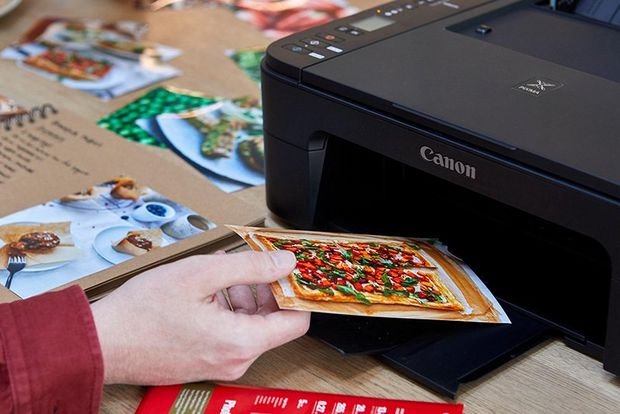 A PIXMA printer prints an image of a sweet potato tart. A child takes the image from the printer.
