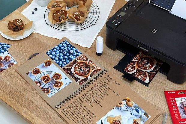 A top-down shot of a printer, a recipe book and muffins on a cooling rack.