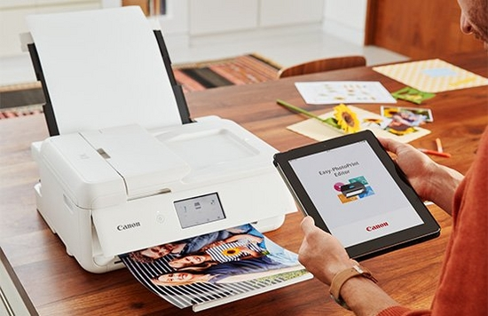 A tablet displays the Canon Easy-PhotoPrint App while a printer prints a picture.