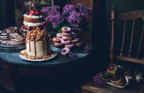 A low-light shot, featuring a table of cakes and flowers.