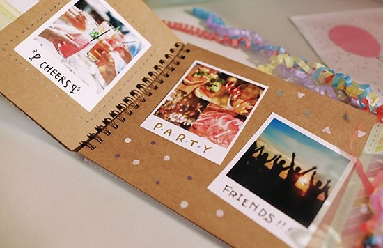 A scrapbook on a table filled with instant camera prints.