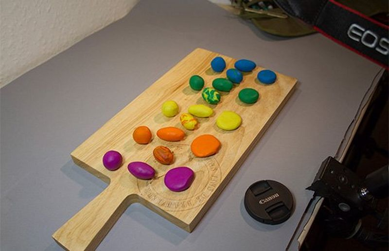 A wooden chopping board with balls of colourful clay spread along it.