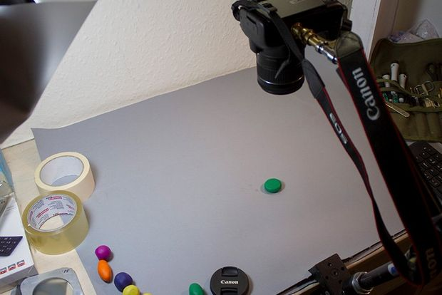 An EOS camera on a tripod pointing down at a small ball of green clay on a tabletop.