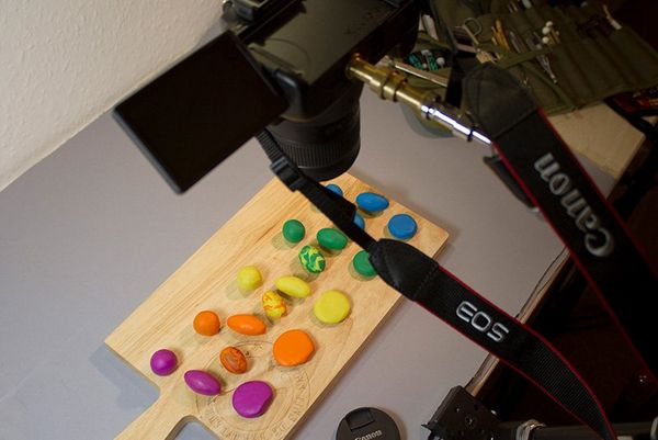 A Canon EOS camera on a tripod, pointing down at a chopping board covered with balls of brightly coloured clay.