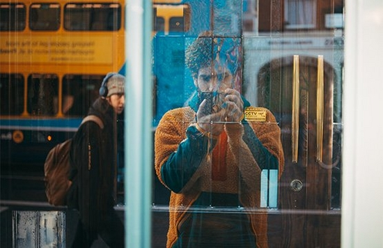 Giuseppe taking a photo of a shop window, showing passers by in the reflection.