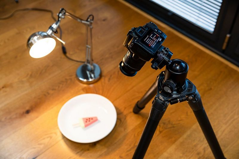 A Canon EOS 250D set up on a tripod facing an ice cream shaped like a slice of watermelon on a plate, with a desk lamp to one side.