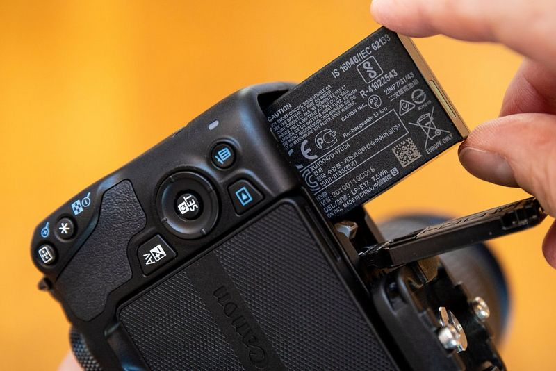 A battery being inserted into a Canon EOS 250D.