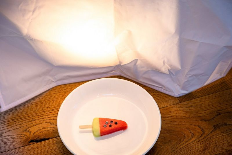 A desk lamp shines through a piece of fine gauze fabric, illuminating an ice cream on a plate.