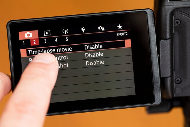 A user's finger selecting Time-lapse movie mode on a Canon camera's vari-angle touchscreen.
