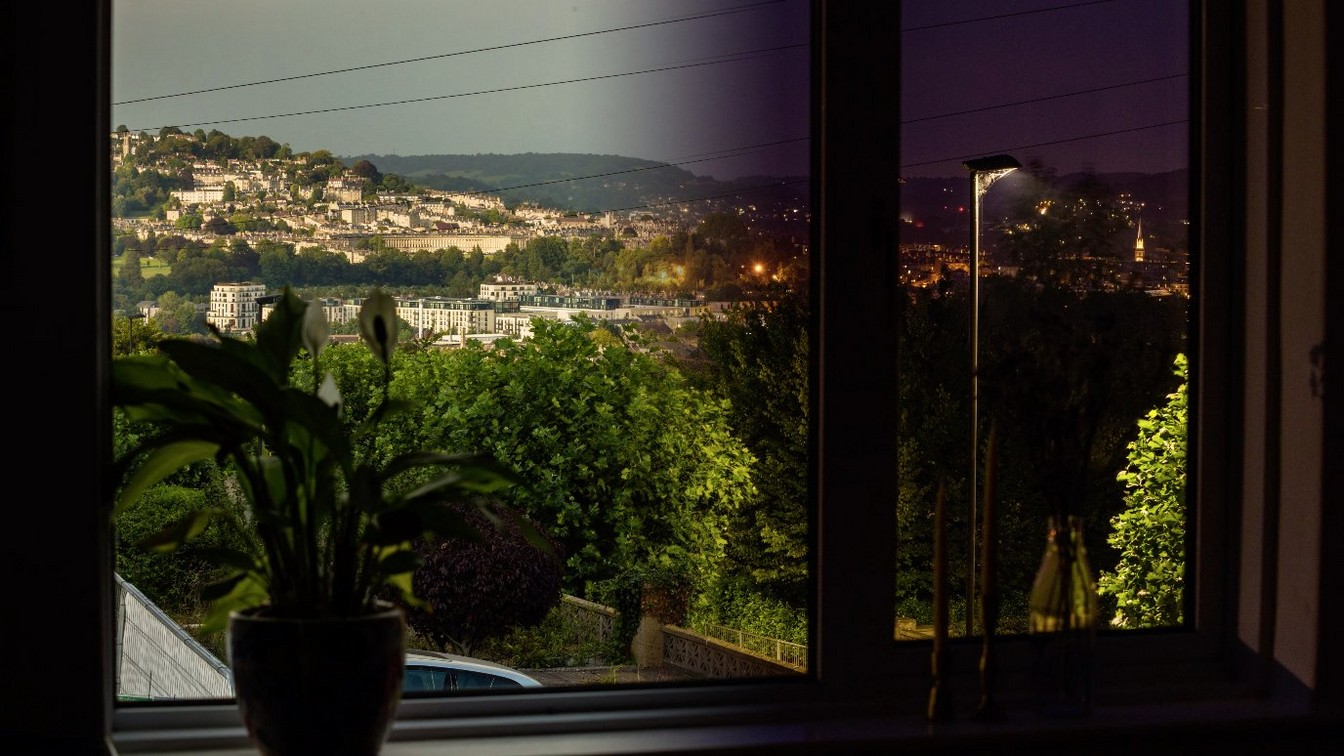 A composite image representing a time-lapse of the scene through a window from day to night.