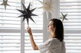 A women touches a paper star hanging from her ceiling.