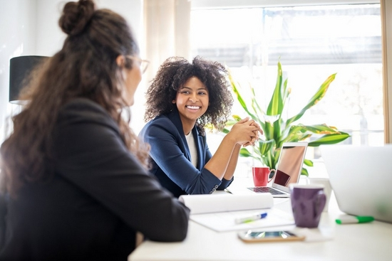 Woman smiles at a colleague while both sat at a white desk with a bright green plant.