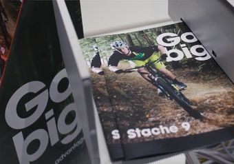Stack of marketing brochures featuring a man riding a mountain bike in the forest, with the headline 'Go big'