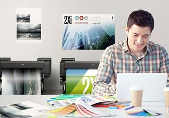 Man wearing a check shirt sitting at a white laptop, surrounded by two digital printers and colour charts spread out on the desk.