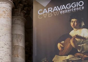 Two light-coloured stone pillars with a banner advertising the CARAVAGGIO experience, with an image of one of the artist's paintings – a woman dressed in white playing a lute.