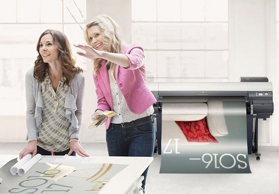 Two women look at printed posters on a table in a white office, in front of a digital printer