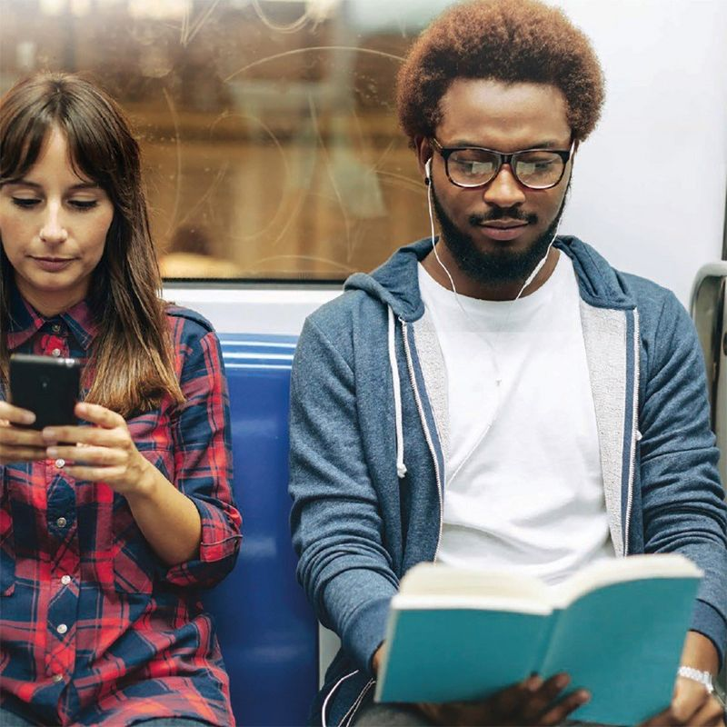 A woman in a check shirt looks at her smartphone and a man wearing a hoodie and white earphones reads a book on a train
