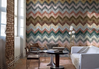 Image of a room with one wall exposed brick, and one covered with digitally printed wallpaper in multi-coloured chevrons, a round table, two chairs and a white sofa