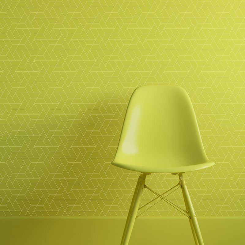 Bright green plastic chair in front of a wall covered with digitally printed wallpaper in bright green with a fine-lined geometric print.