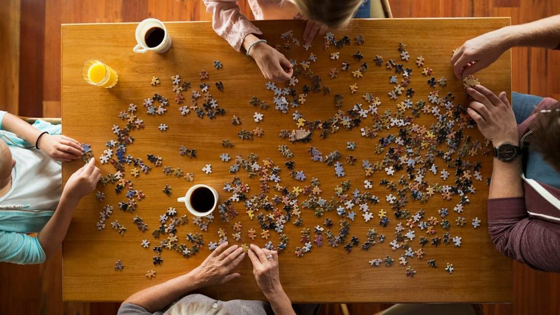 Group of friends completing puzzle on a table with coffee