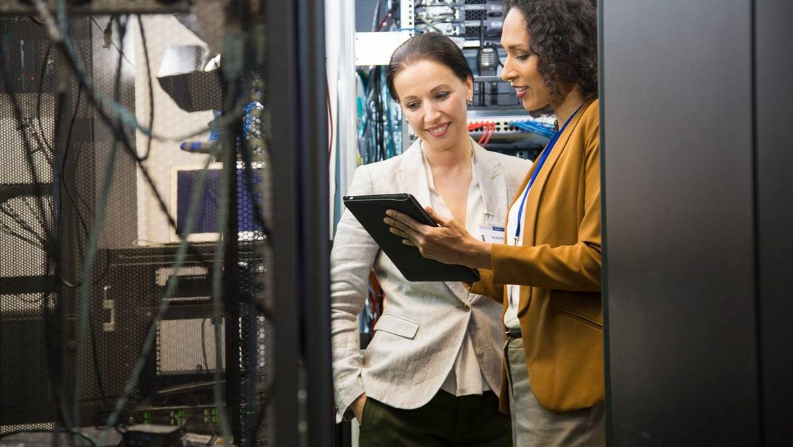 Two female office employees talking in a server room