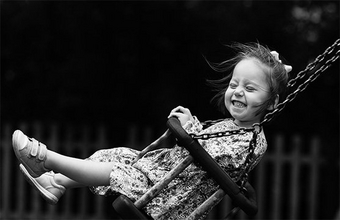 Black and white portrait of a smiling child playing on a swing.
