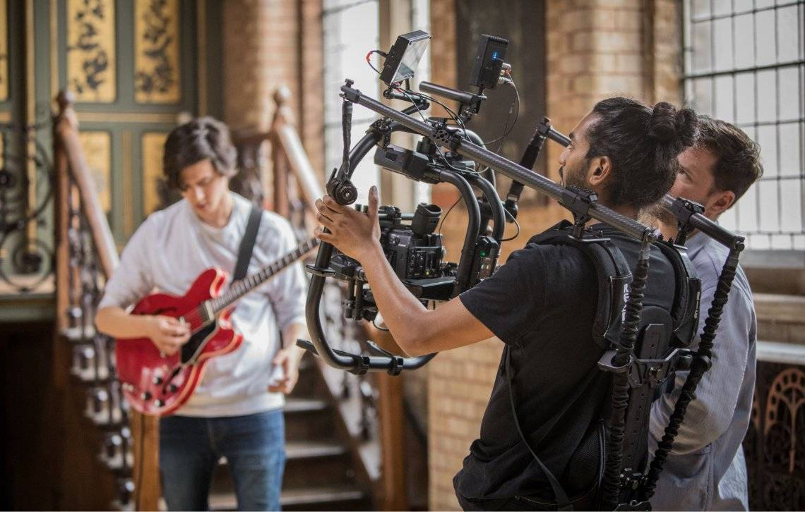 Canon video camera in action whilst filming ricky patel with his guitar.