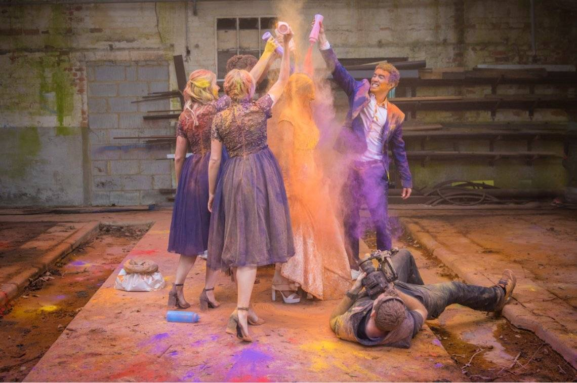 Group of people pouring coulored powder on a woman.