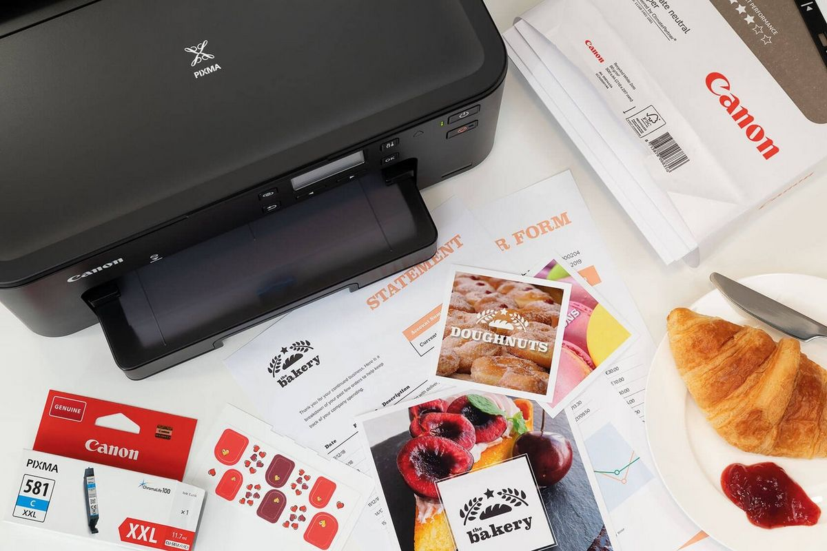 Canon PIXMA Printer on a desk surrounded by printer prints