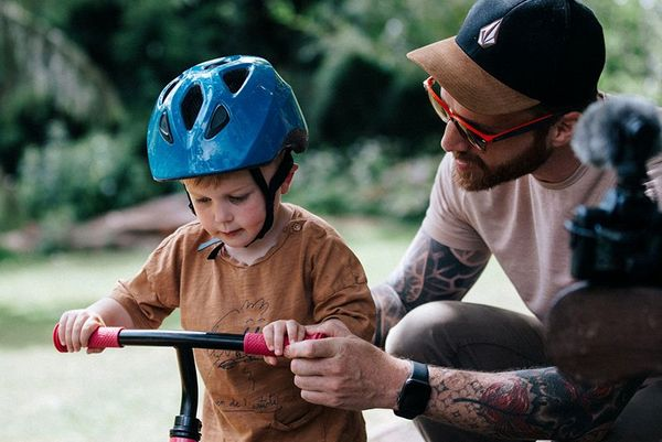 Stef Michalak helping his son hold onto the handles of his balance bike. Stef's EOS M50 is resting on the arm of a bench.