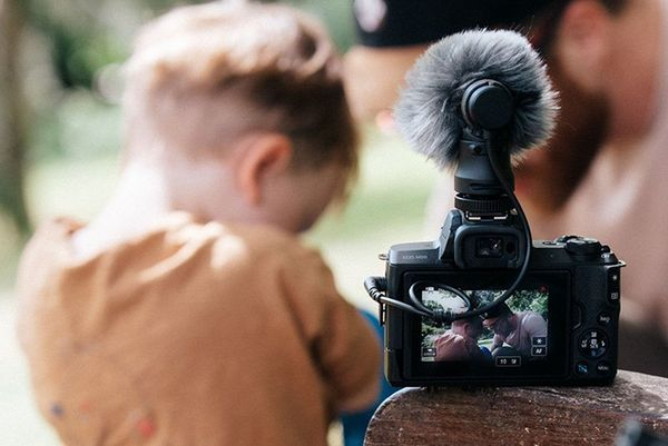 The Canon EOS M50 with the Canon DM-E100 mic attached, positioned on the arm of a bench behind Stef Michalak and his son.