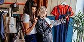 Two women pose in front of a camera in a clothes shop.