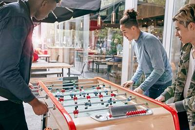 Three people play table football in a communal space