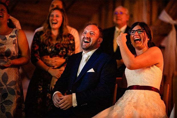 A bride and groom sat together and laughing.